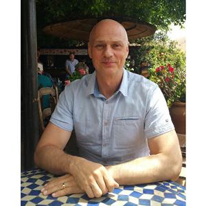 uśmiechnięty mężczyzna siedzący przy stoliku, trzymający ręce na stole, koszula niebieska z krótkim rękawkiem